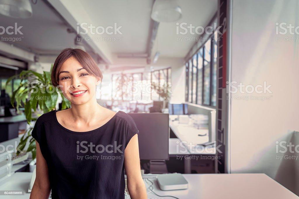 Portrait of happy businesswoman standing in office stock photo