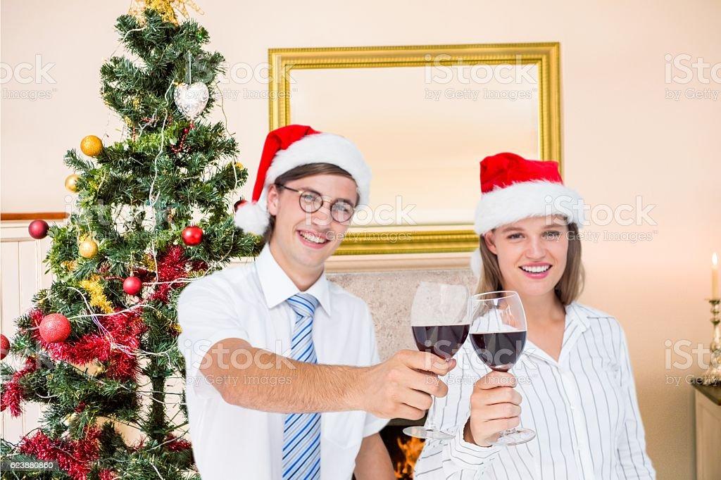 Portrait of happy couple in santa hat toasting red wine stock photo