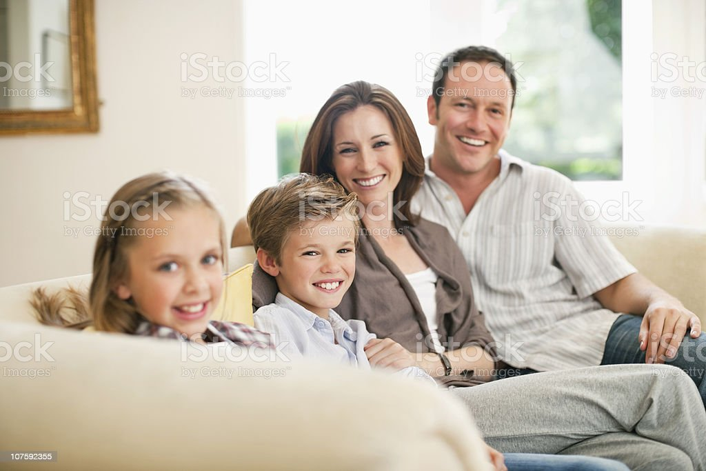 Portrait of happy couple with kids (8-11) sitting on couch at home, smiling royalty-free stock photo