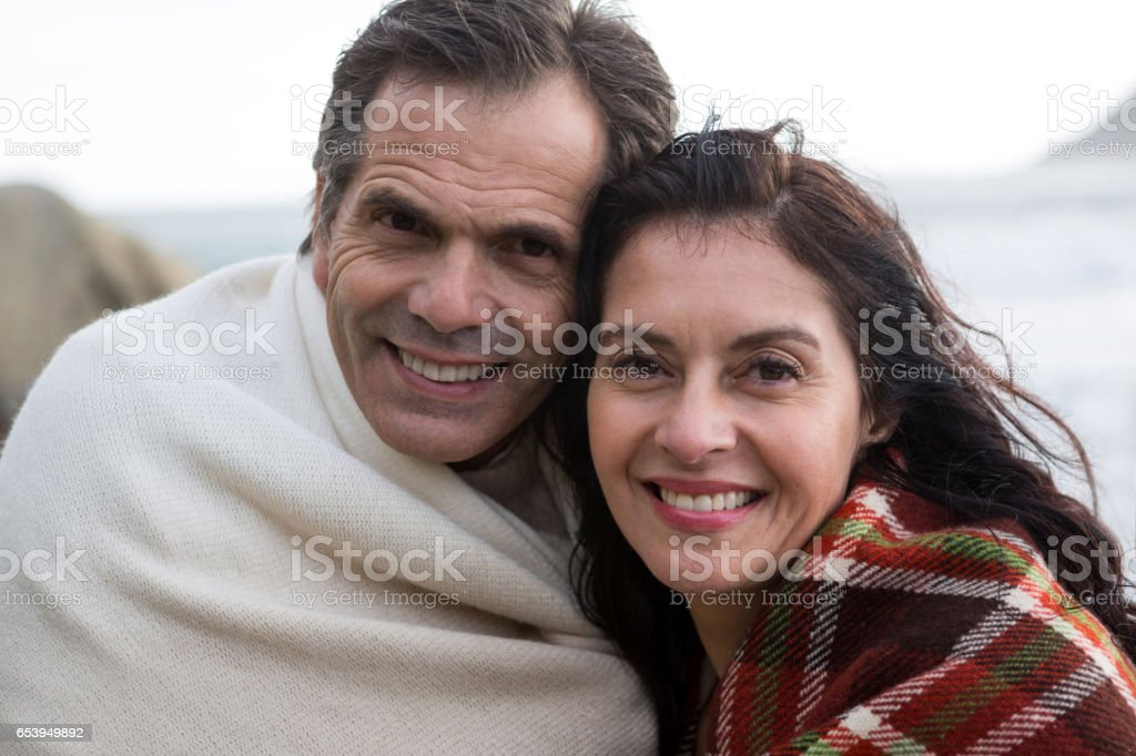 Portrait of happy couple wrapped in shawl on beach stock photo