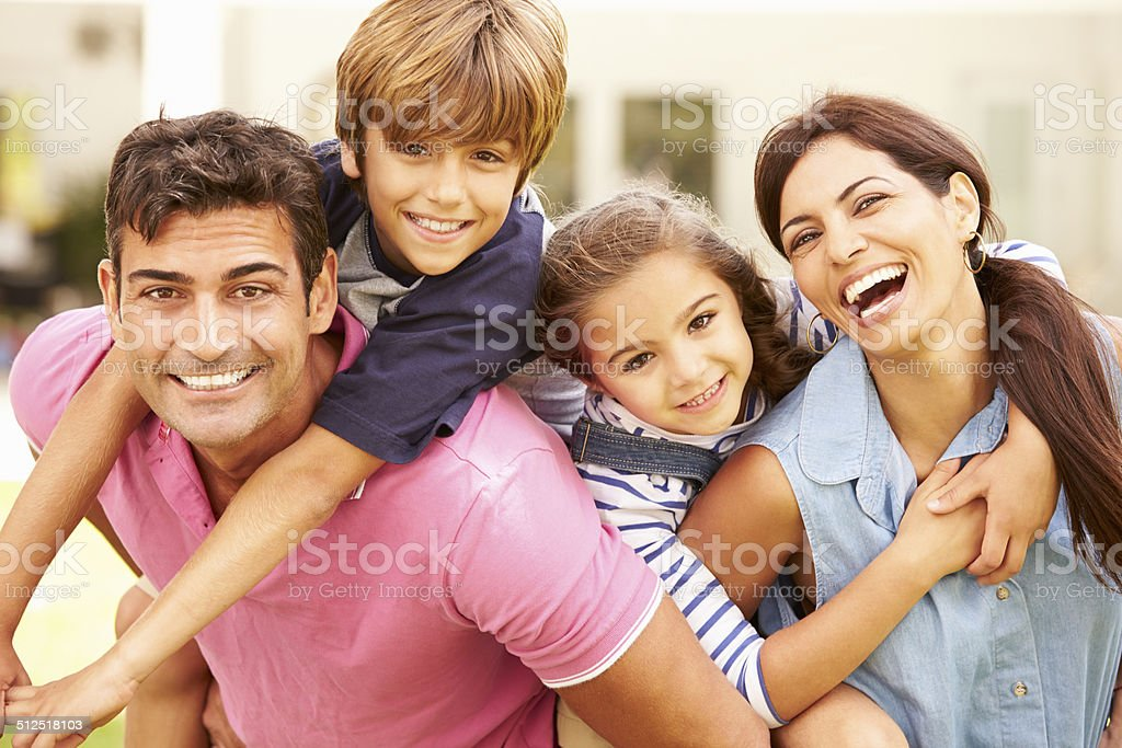 Portrait Of Happy Family In Garden At Home Smiling To Camera