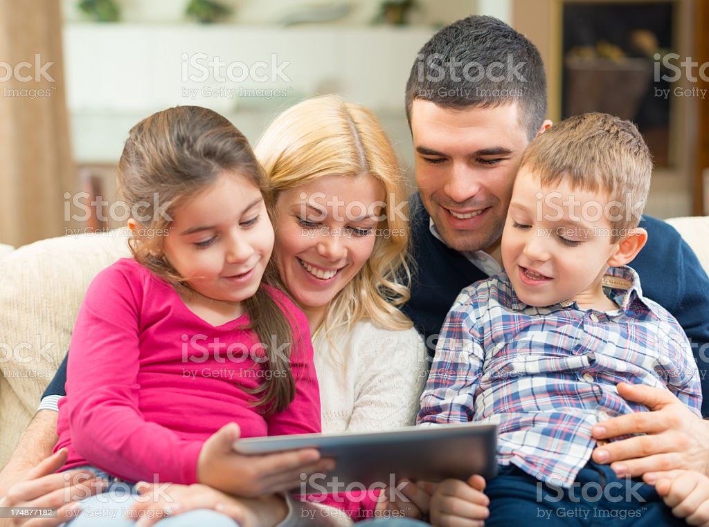 Portrait of happy family playing at digital tablet royalty-free stock photo