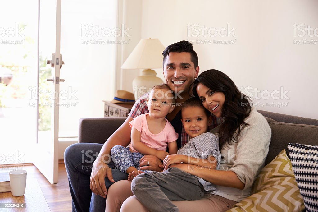 Portrait Of Happy Family Sitting On Sofa In at Home stock photo