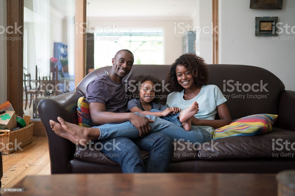 Portrait of happy family sitting on sofa stock photo
