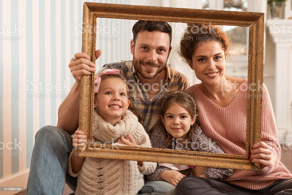 Portrait of happy family through a picture frame. stock photo