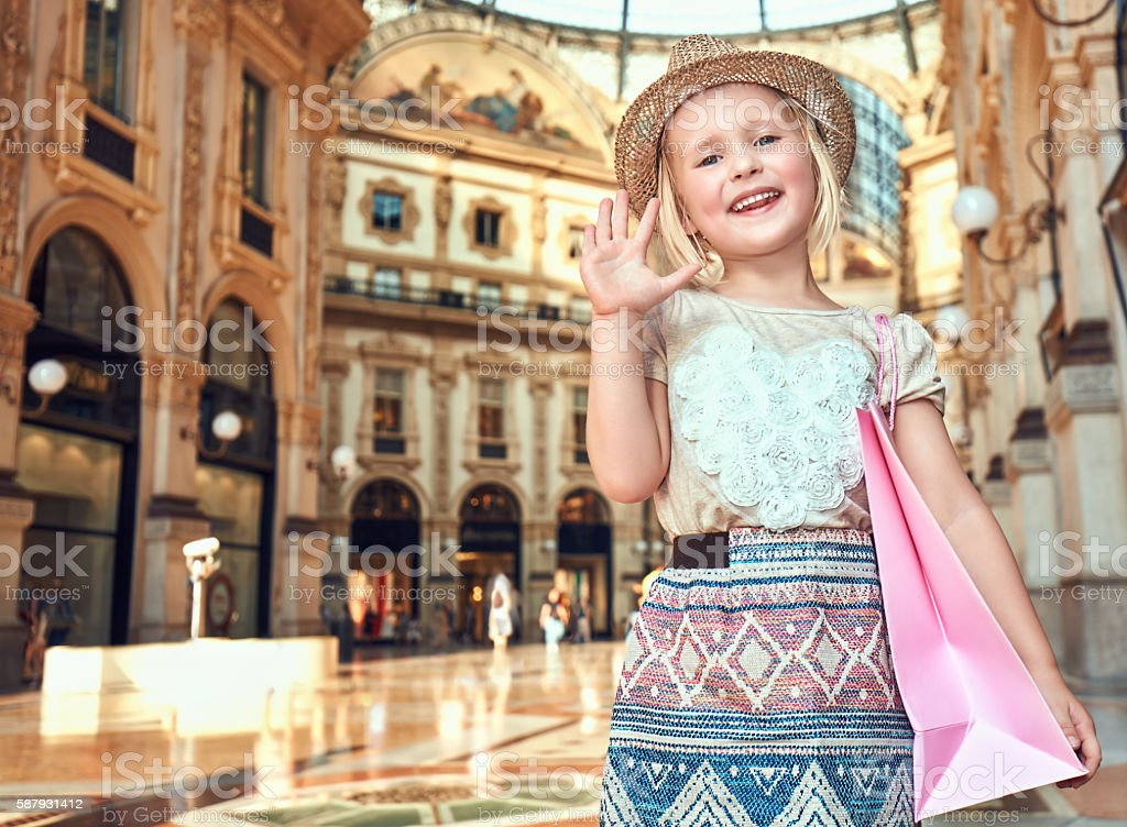Portrait of happy fashion girl with shopping bag hand waving stock photo