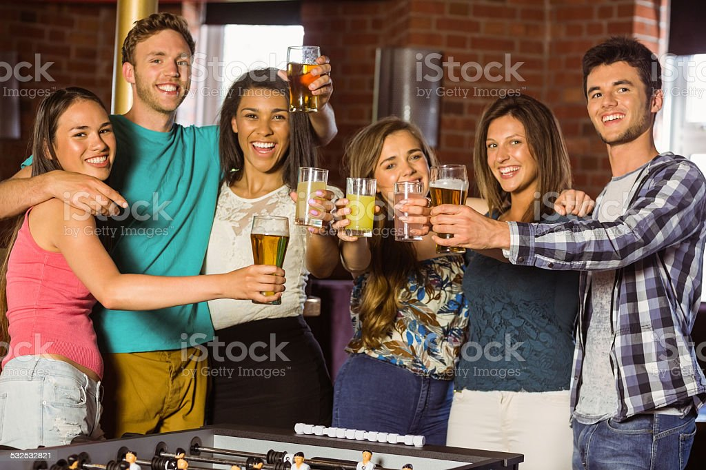 Portrait of happy friends toasting with mixed drink and beer stock photo