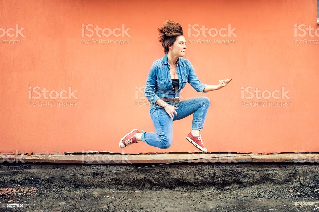 Portrait of happy girl jumping and singing, hot summer day stock photo