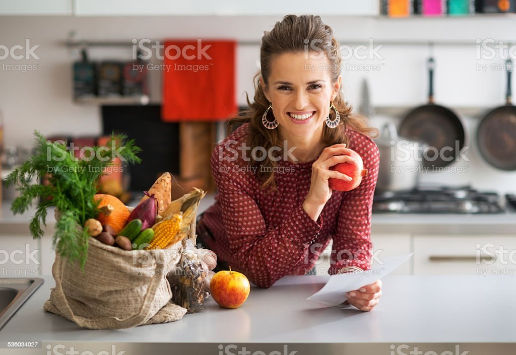 Portrait of happy housewife holding grocery shopping checks stock photo
