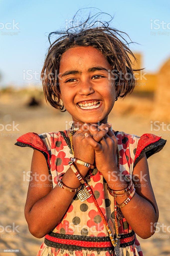 Portrait of happy Indian little girl, desert village, Rajasthan, India. stock photo