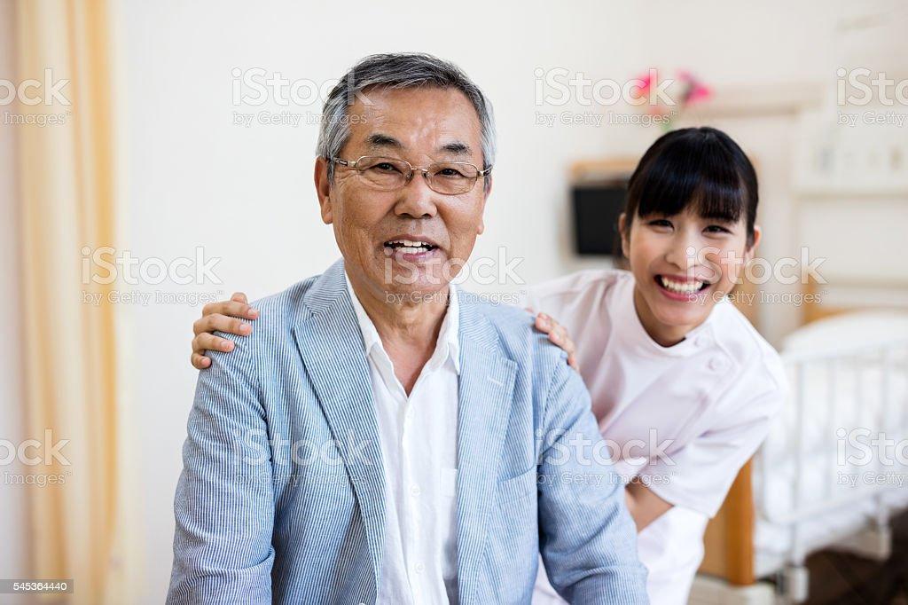 Portrait of happy japanese senior man with nurse in hospital stock photo
