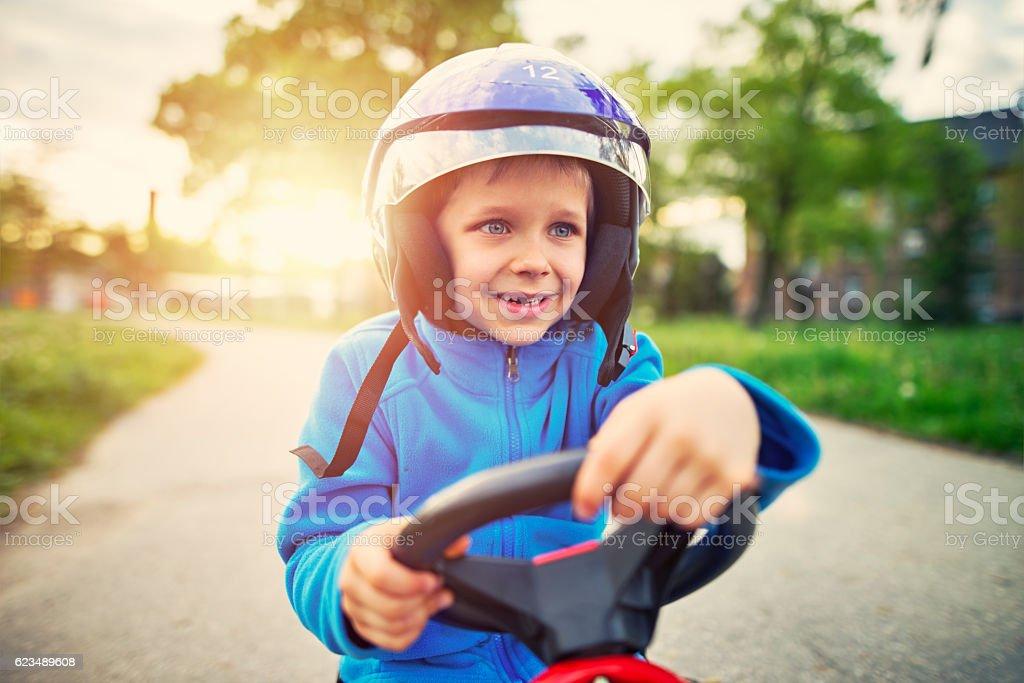 Portrait of happy little boy riding a fast go-kart. stock photo