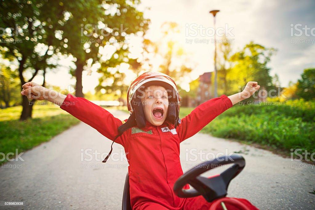 Portrait of happy little boy winning a go-kart race stock photo