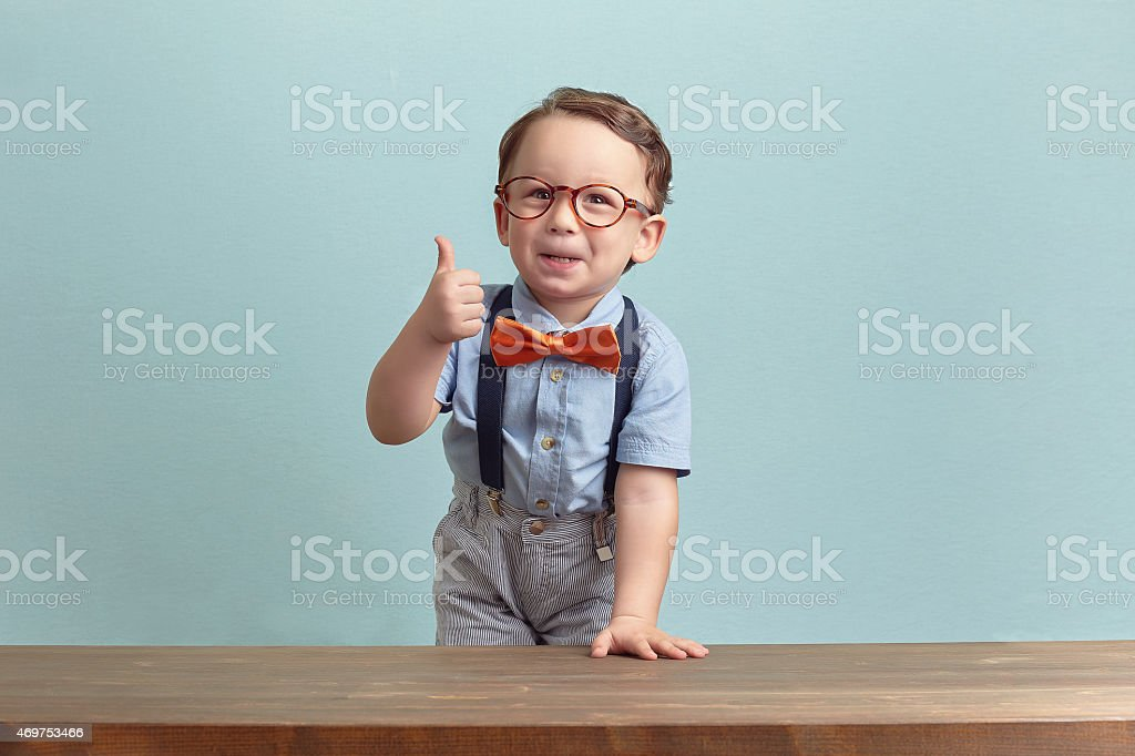 Portrait of happy little boy with glasses giving thumbs up stock photo