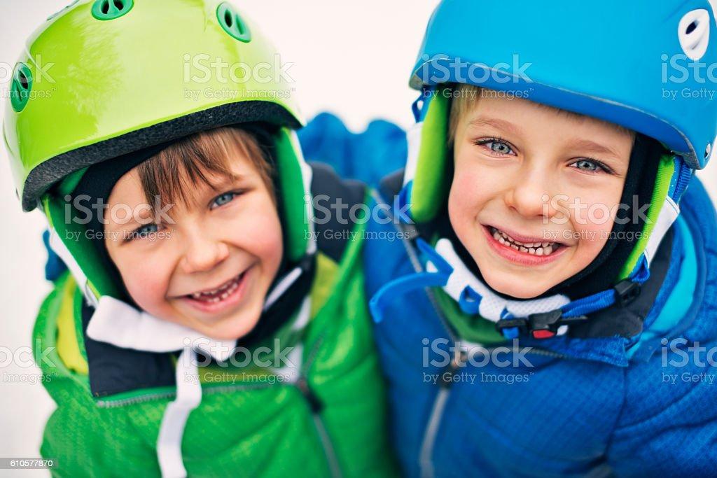 Portrait of happy little boys wearing ski helmets stock photo