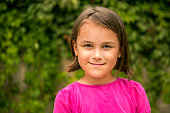 Portrait of happy little girl smiling against tree area