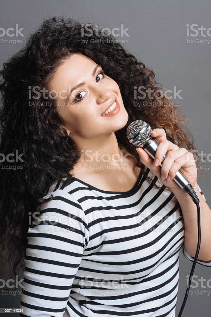 Portrait of happy looking girl holding microphone stock photo