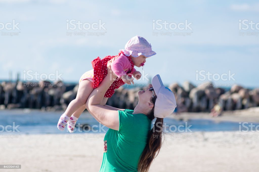 Portrait of happy loving mother and her baby girl child outdoors at the beach on sunny day stock photo