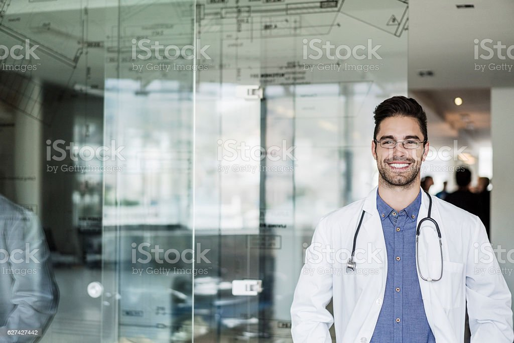 Portrait of happy male doctor standing in clinic stock photo