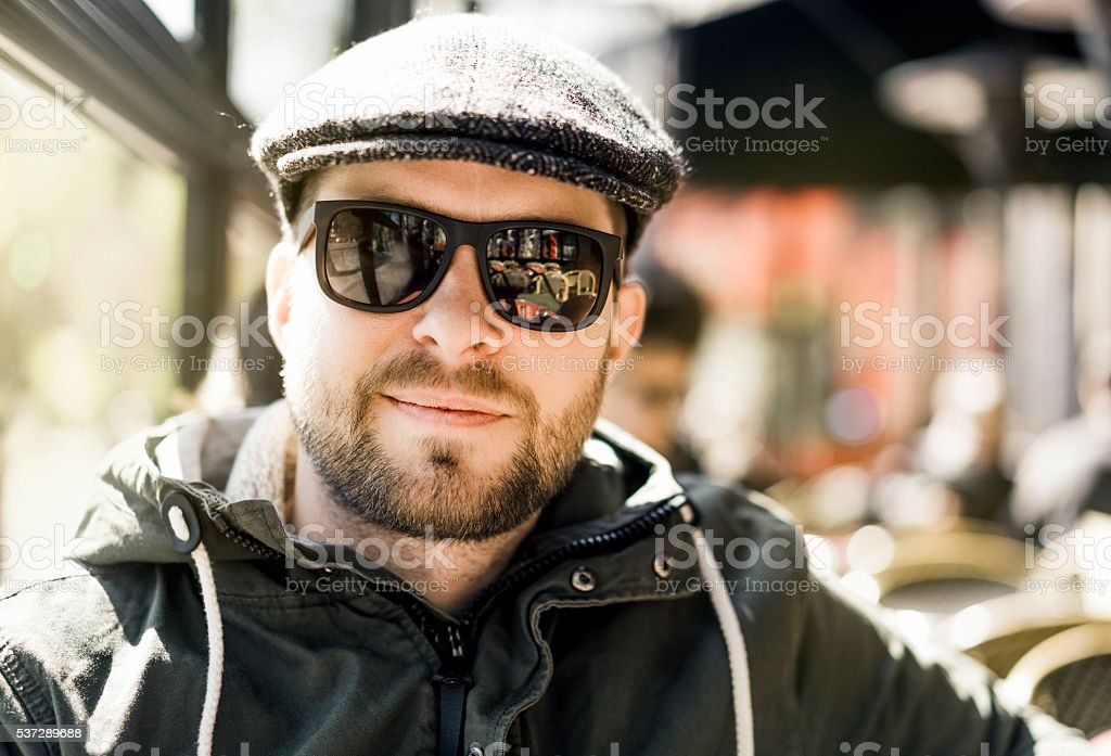 Portrait of happy man wearing sunglasses and cap stock photo