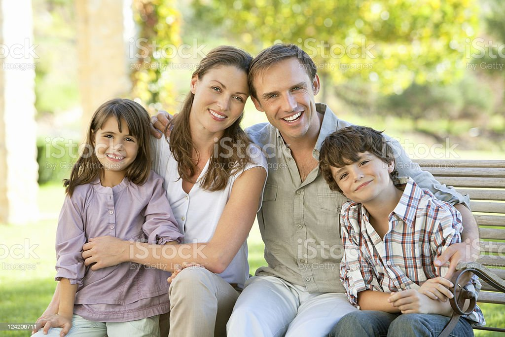 Portrait of happy mid adult couple with two children in park royalty-free stock photo