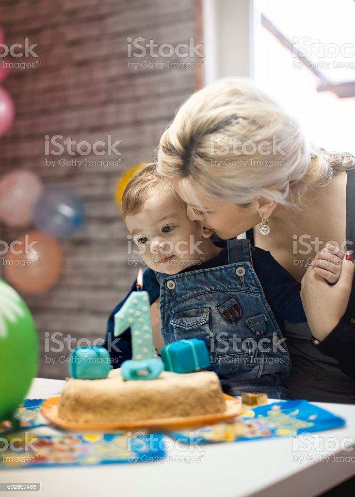 portrait of happy mom and baby with birthday cake stock photo