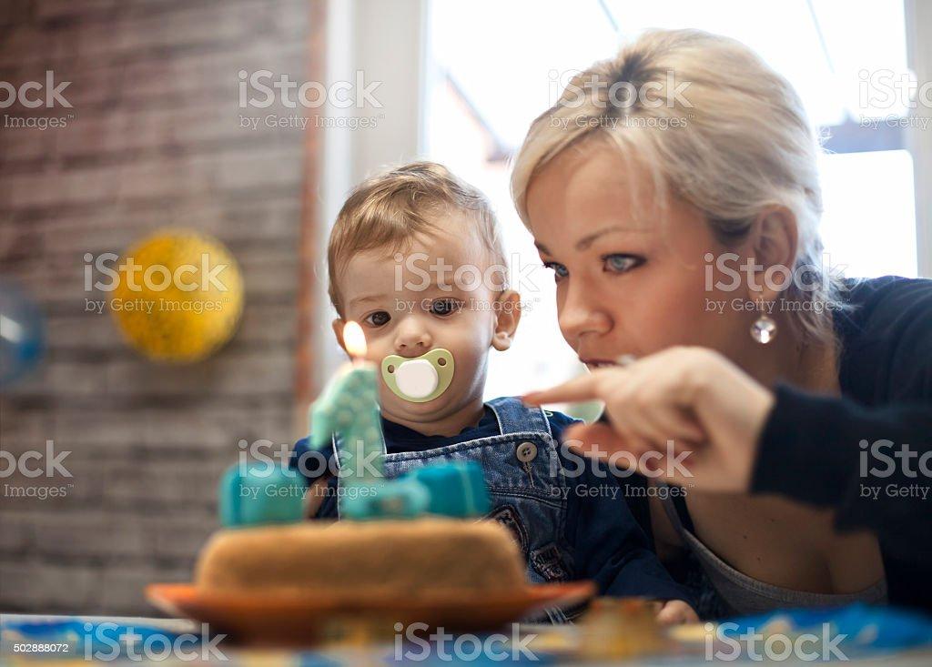 portrait of happy mom and baby with birthday cake stock photo