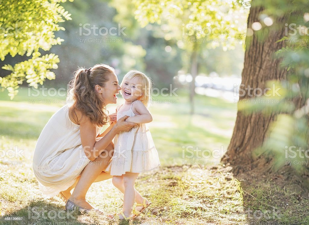 portrait of happy mother and baby playing outdoors stock photo