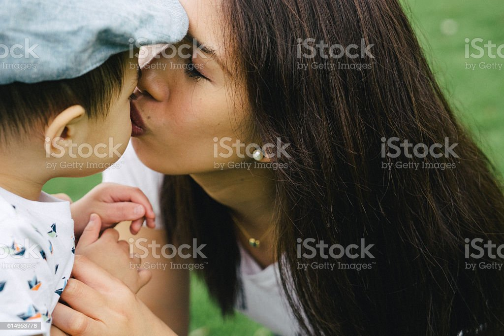 Portrait of happy mother kissing her son outdoors stock photo