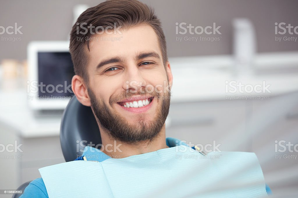 Portrait of happy patient in dental chair. stock photo