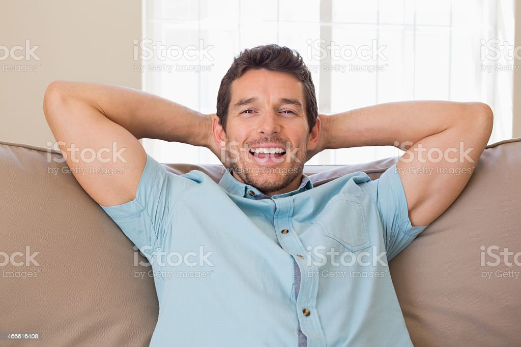 Portrait of happy relaxed man sitting on couch stock photo