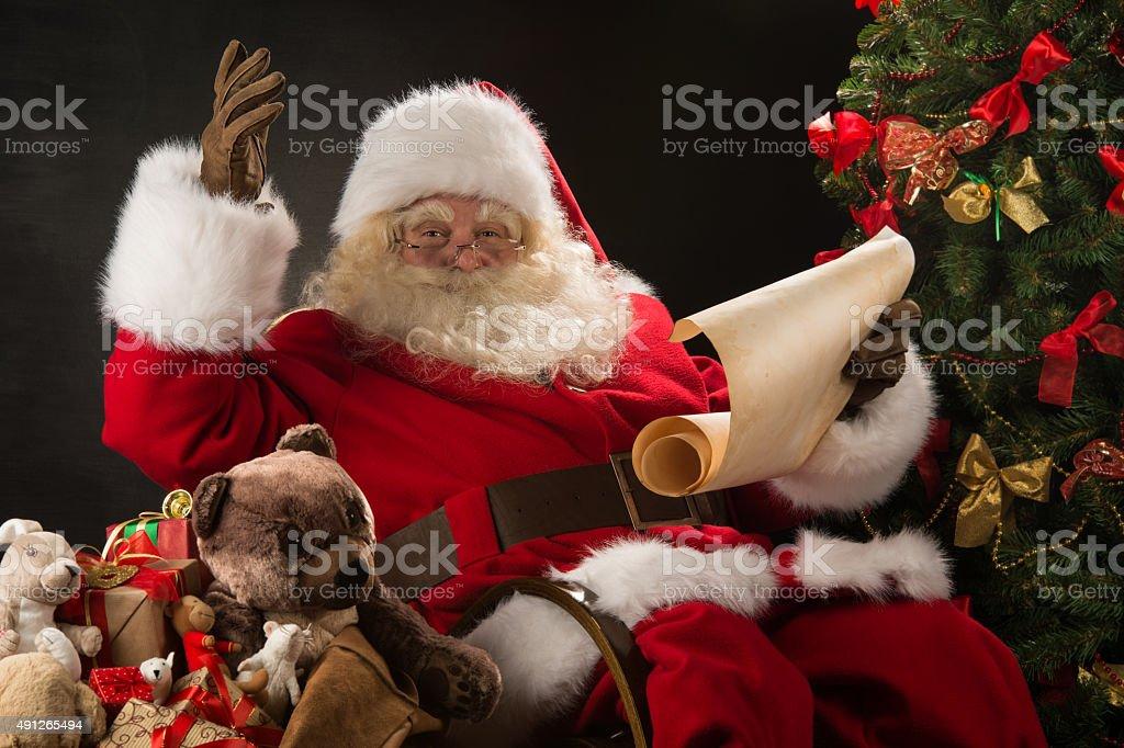 Portrait of happy Santa Claus reading Christmas letter stock photo