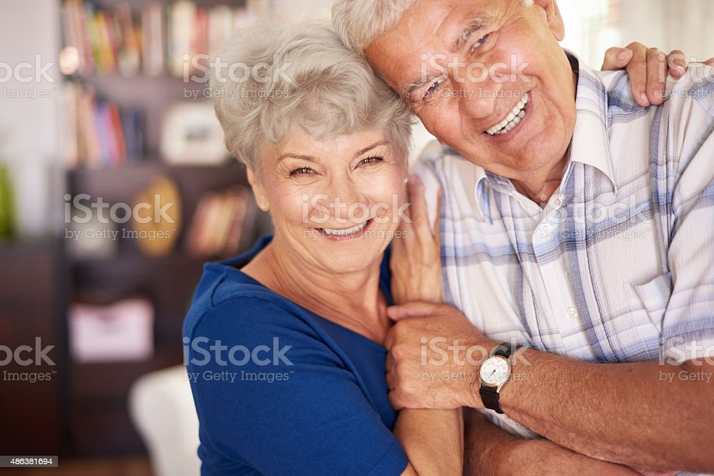 Portrait of happy senior couple in arms stock photo