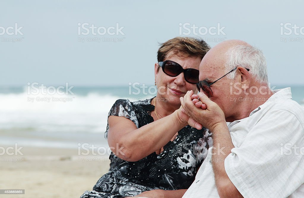 Portrait of happy senior couple sitting together on a beach royalty-free stock photo