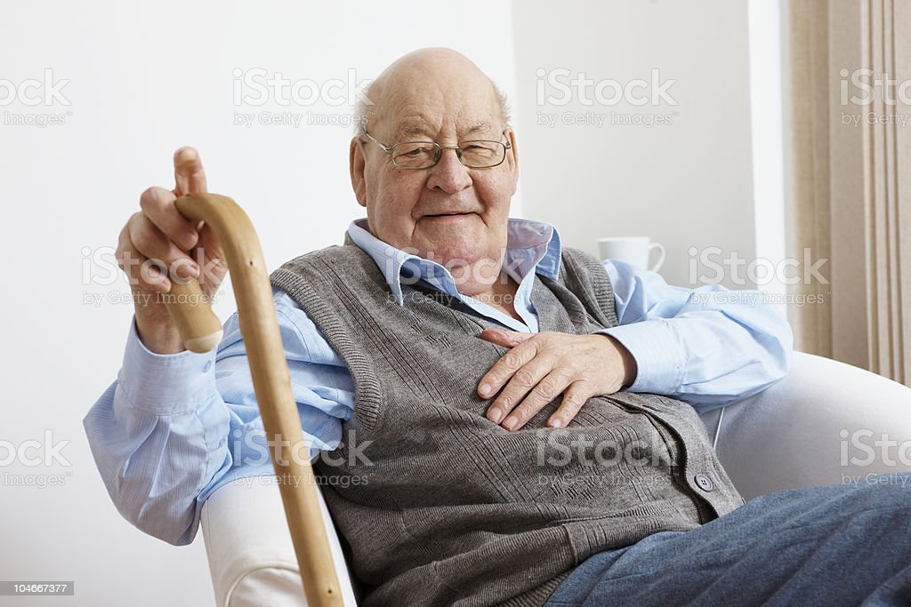 portrait of happy senior man sitting in chair stock photo