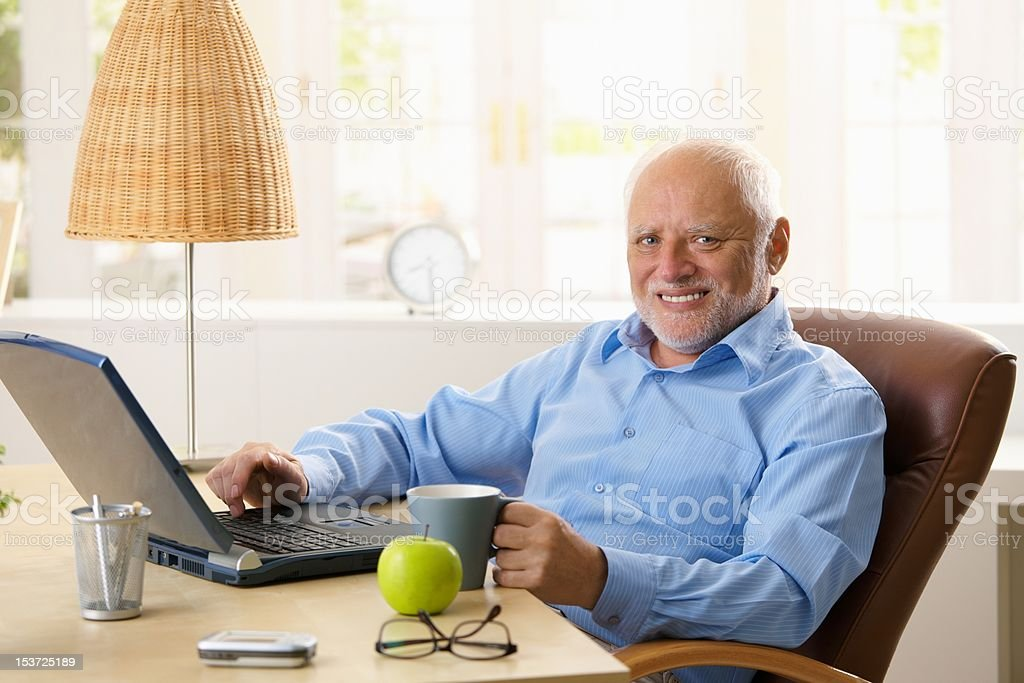 Portrait of happy senior man with computer royalty-free stock photo