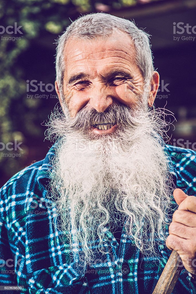 Portrait of Happy Senior Man with Extremely Long Beard Outdoors stock photo