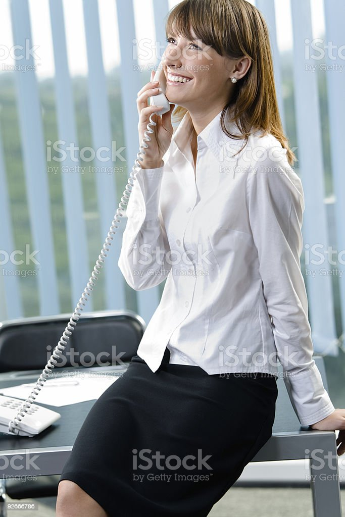 Portrait of happy smiling businesswoman on phone at office royalty-free stock photo