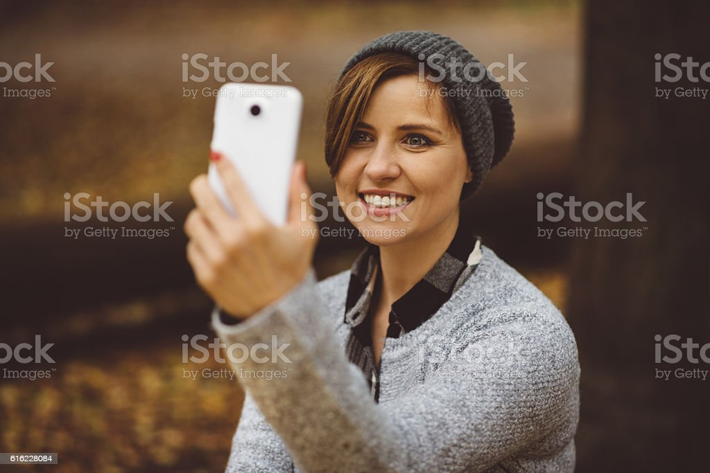Portrait of happy, smiling woman sitting alone in the forest stock photo
