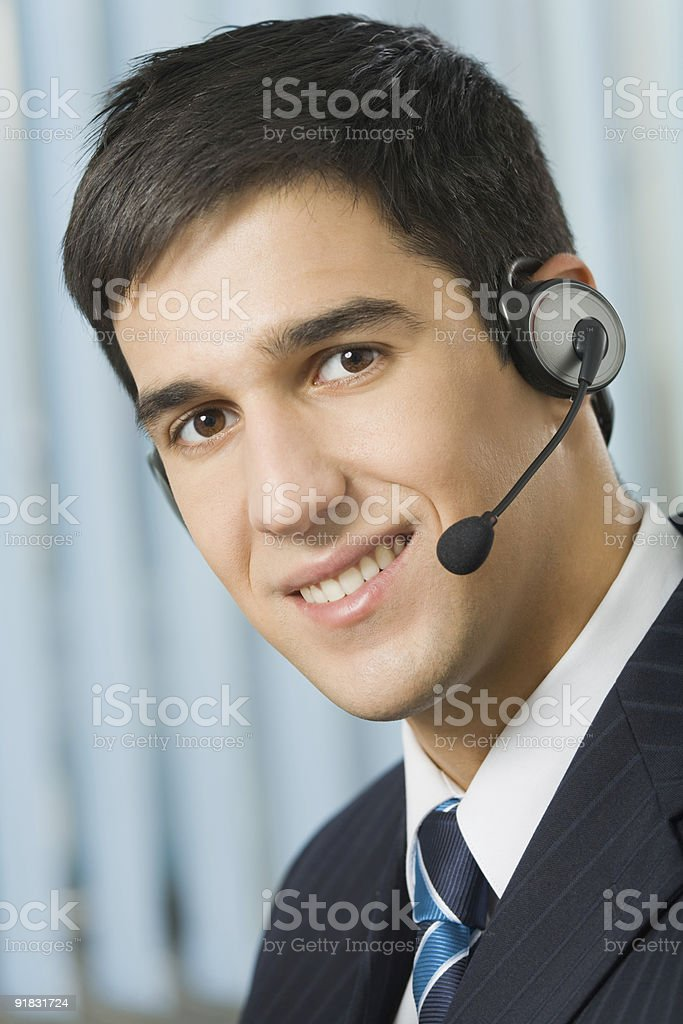 Portrait of happy support operator in headset at workplace royalty-free stock photo