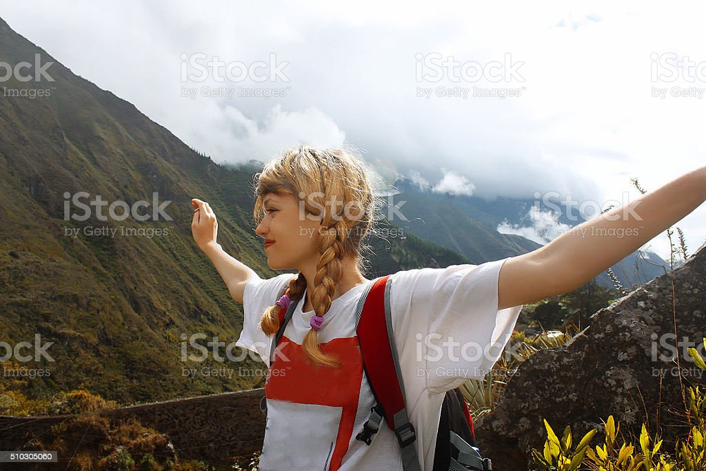 Portrait of happy traveler girl with raised up hands stock photo