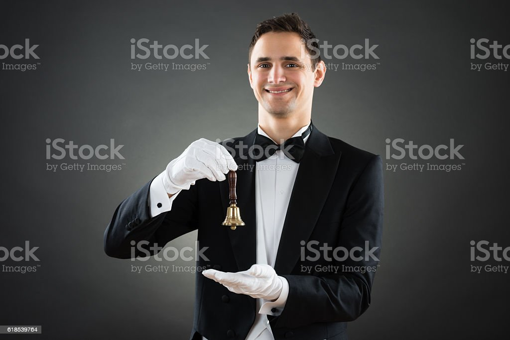 Portrait Of Happy Waiter Holding Ring Bell stock photo