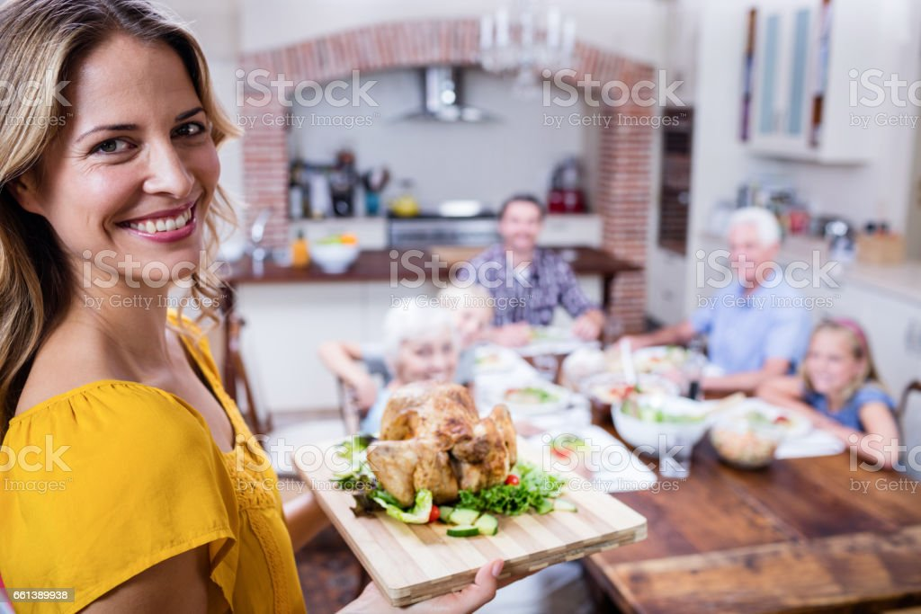 Portrait of happy woman holding a tray of roasted turkey stock photo
