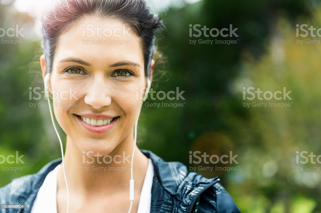 Portrait of happy woman listening to music outdoors stock photo