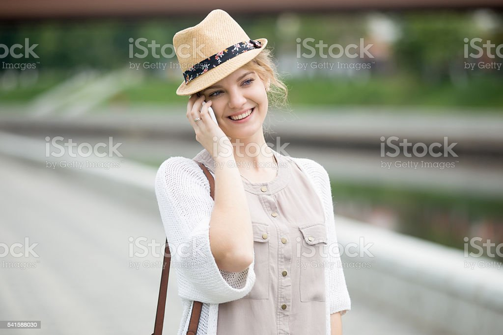 Portrait of happy woman talking on smartphone while walking stock photo