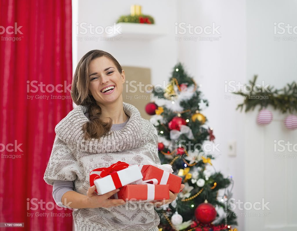 Portrait of happy woman with present boxes near Christmas tree royalty-free stock photo