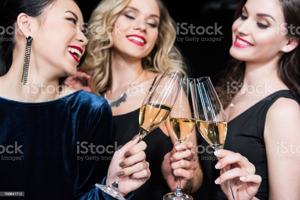 portrait of happy women in stylish dresses clinking glasses with champagne stock photo