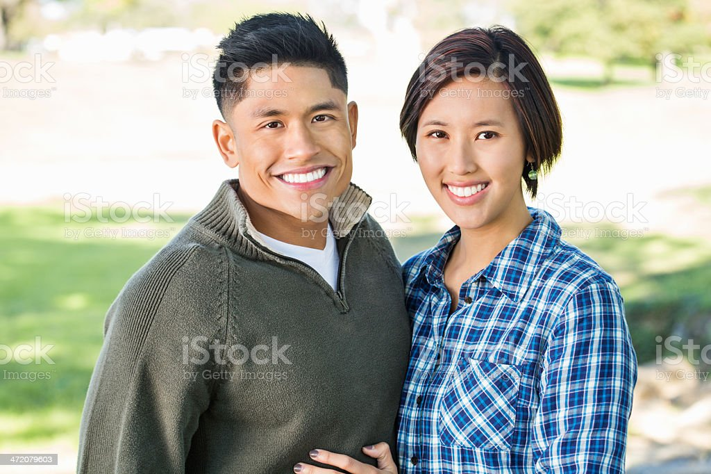 Portrait of happy young Asian couple outdoors at park stock photo