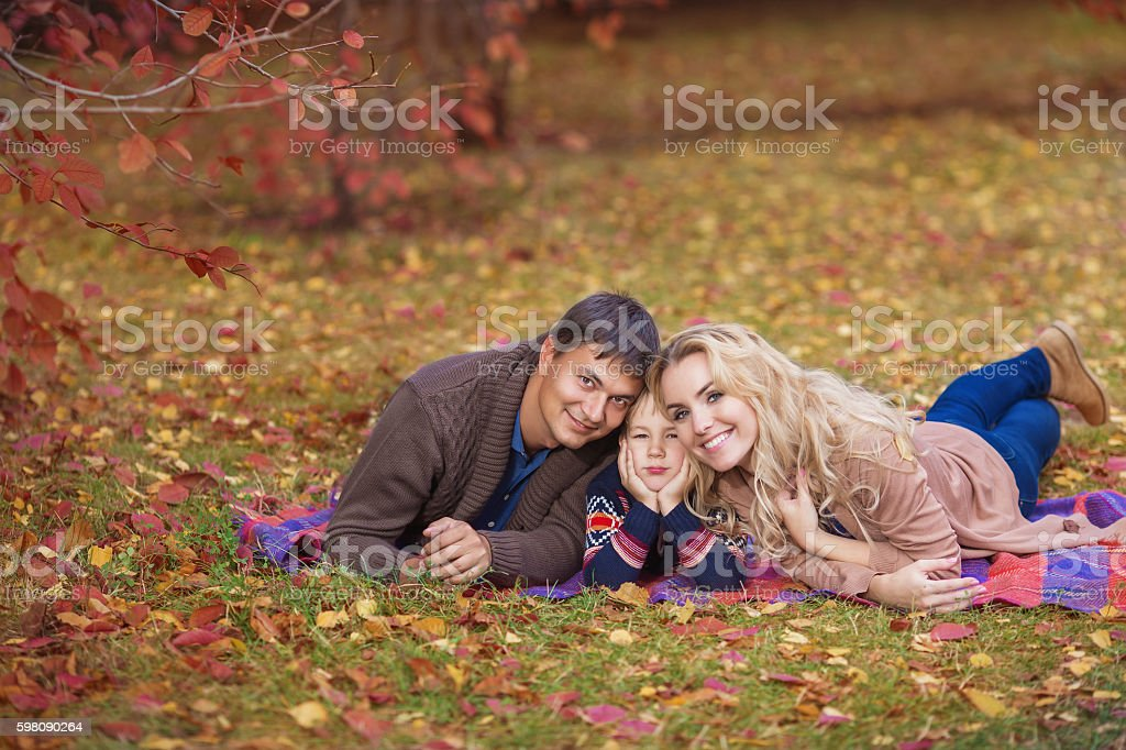 Portrait of happy young family in park in the autumn stock photo