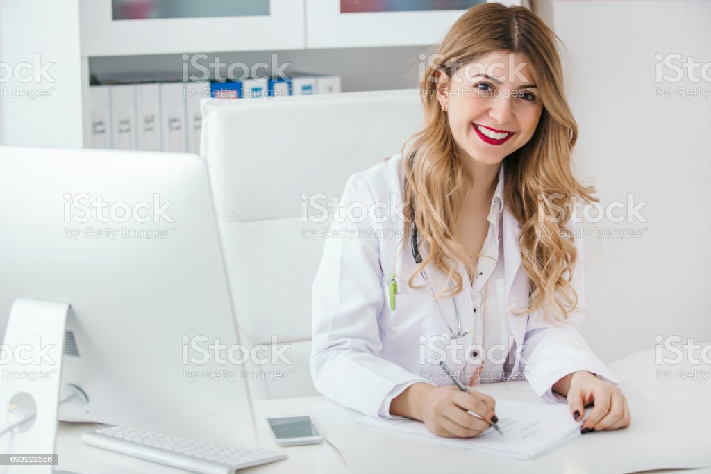 Portrait of happy young friendly doctor writing diagnosis stock photo
